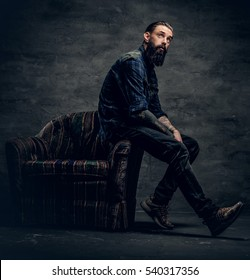 Full body portrait of tattooed, bearded male dressed in a plaid flannel shirt sits on a chair over dark grey background.