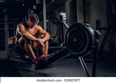 Full body portrait of tired sporty male after workouts on power exercise machine in a gym club.
