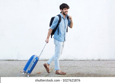 Full body portrait of travel man with bag pulling suitcase