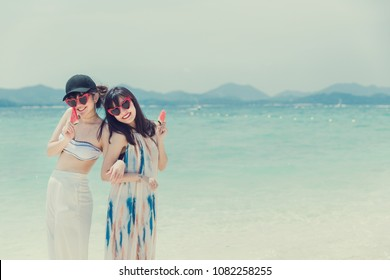 Full body portrait of two young women friends laughing and enjoy on the beach,In the hands holding a fruit.