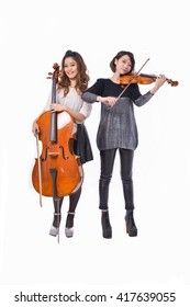 Full body portrait of two young woman is playing the violin