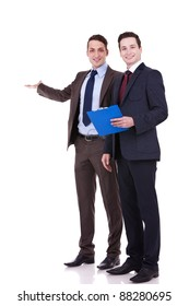 full body portrait of two young business men presenting something at their back