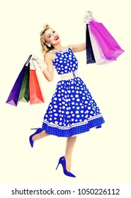 Full body portrait of woman in pin-up style blue dress in polka dot holding shopping bags, over yellow background. Caucasian blond model posing in sales, consumer, retro fashion and vintage concept.