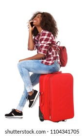 Full body portrait of young african woman sitting on suitcase and talking on mobile phone over white background