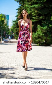 Full body portrait of a young beautiful brunette woman walking in summer park
