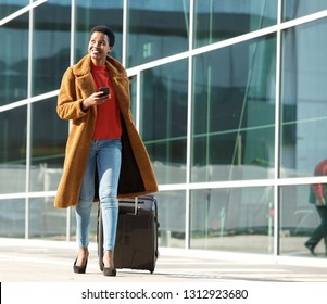 Full body portrait of young black woman walking outdoors with luggage and mobile phone