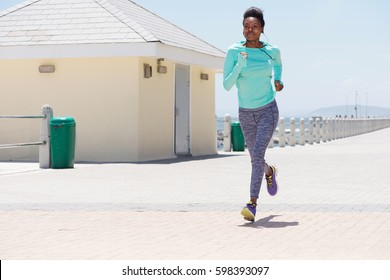Full body portrait of young black woman running outdoors path
