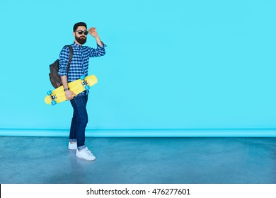 Full body portrait of young fashionable hipster man posing over blue background with copy space. Bearded male holding yellow skateboard and smiling