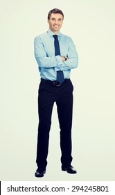 Full body portrait of young happy smiling businessman, in blue confident business wear