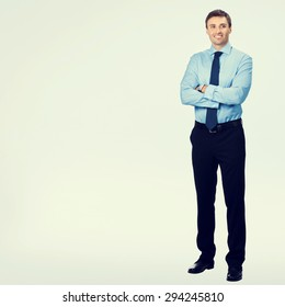 Full body portrait of young happy smiling businessman, in blue confident business wear, with blank copyspace area for slogan or text message