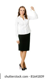 Full body portrait of young happy smiling business woman or real estate agent showing keys from new house, isolated on white background