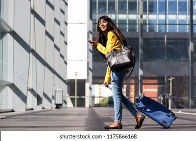 Full body portrait of young Indian woman walking with mobile phone and bags at station