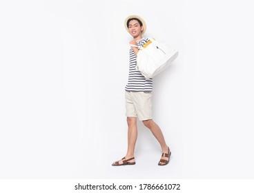 Ganzkörper Portrait von jungen Männern in gestreiftem T-Shirt und weißen Hosen Hosen kurze Hosen mit Handtasche, Hut, braune Schuhe, die im Studio laufen