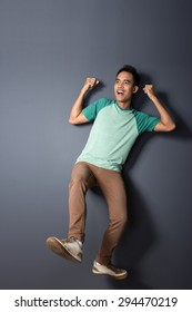 full body portrait of young man floating and pretending to use a parachute