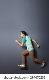 full body portrait of young man running in the air with copy space