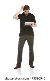 Full body portrait of young man scratching his head while looking at a digital tablet computer