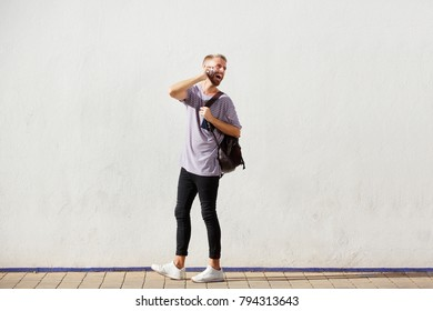Full body portrait of young man walking and talking on cellphone