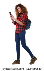Full body portrait of young woman walking on isolated white background with mobile phone and bag
