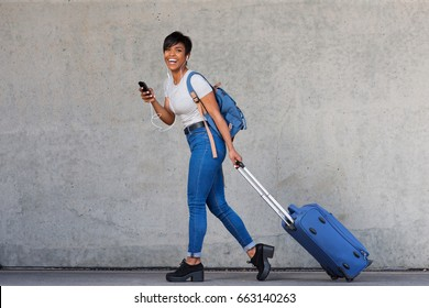 Full body portrait of young woman walking with travel bag and mobile phone
