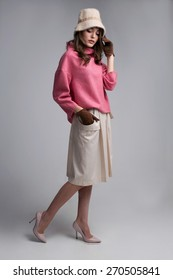 Full body pretty woman in pink sweater posing on grey background
