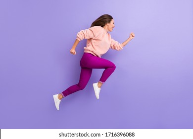 Full body profile photo of active cheerful lady jumping high rushing speed finish line race competition wear casual warm fluffy sweater pants shoes isolated purple color background