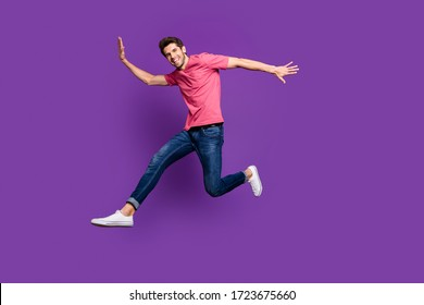 Full body profile photo of attractive guy jumping high up running shopping center sale season see friend street wear casual pink t-shirt jeans shoes isolated purple color background