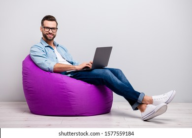 Full body profile photo of funny guy holding notebook browsing chatting colleagues sitting comfy soft armchair wear specs casual denim outfit isolated grey color background