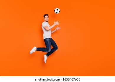 Full body profile photo of funny guy jump high up catch football ball addicted fan goalkeeper wear striped t-shirt jeans sneakers isolated bright orange color background