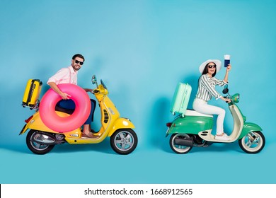 Full body profile photo of funny lady guy two people drive retro moped suitcases show tickets carry pink inflatable circle formalwear outfit sun cap specs isolated blue color background