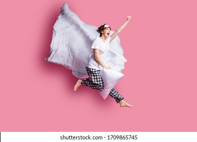 Full body profile photo of funny lady jump high pillow between legs blanket flight moving ahead wear sleep mask white t-shirt plaid pajama pants barefoot isolated pink color background