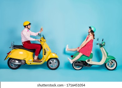 Full body profile photo of funny lady guy two people sitting vintage moped vacation together take pictures telephone bloggers wear retro clothes headgear isolated blue color background