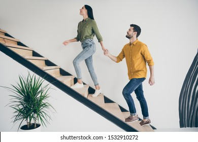 Full body profile photo of handsome guy and his pretty lady leading macho to bedroom going up stairs in modern interior hotel room indoors wear casual clothes