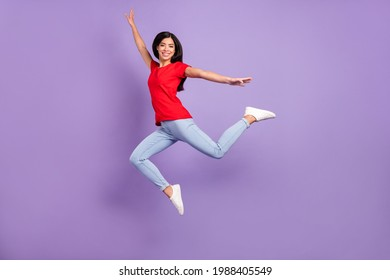 Full body profile photo of nice young brunette hairdo lady jump wear red t-shirt jeans isolated on violet color background