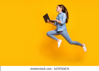 Full body profile photo of pretty business lady jump high holding notebook hands hurry work browsing laptop wear casual denim outfit white sneakers isolated yellow color background