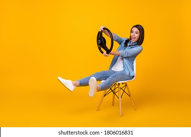 Full body profile photo of pretty funny lady good mood sit chair spread legs playing hold steering wheel riding imagine car wear casual denim shirt shoes isolated yellow color background