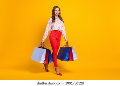 Full body profile photo of pretty cheerful lady walking hands carry bags isolated on yellow color background