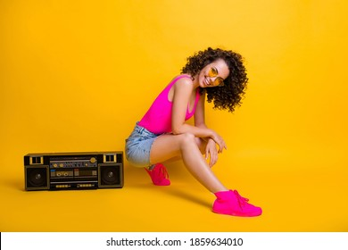 Full body profile photo of tender funny dj lady sitting side near boom box holiday party summer chill event wear sun specs pink singlet skirt sneakers isolated shine yellow color background