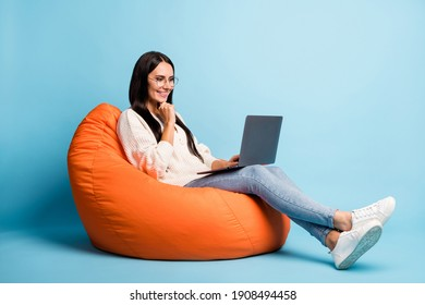 Full body profile portrait of cheerful person hand on chin laptop look screen isolated on blue color background