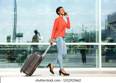 Full body profile portrait of happy female traveler walking  with suitcase bag and cellphone