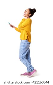 Full body profile portrait of laughing young woman walking with mobile phone on white background