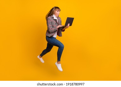 Full body profile portrait of shocked lady open mouth staring laptop isolated on yellow color background