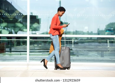 Full body profile portrait of young african american woman walking with suitcase and cellphone