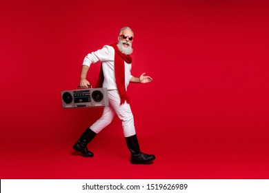 Full body profile side photo of excited grandfather going holding audio cassette wearing white sweater isolated over red background