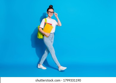 Full body profile side photo of positive college student girl go copyspace hurry scholar lectures hold copybooks bag wear white stylish trendy clothes isolated bright shine color background