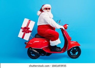 Full body profile side photo of stylish modern white grey hair bearded santa claus drive scooter deliver x-mas time eve gift box wear suspenders overalls isolated blue color background