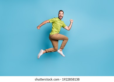 Full body profile side photo of crazy funky positive man jump up run empty space isolated on blue color background