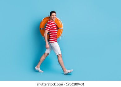 Full body profile side photo of happy man hold orange lifesaver ring go copyspace isolated on blue color background