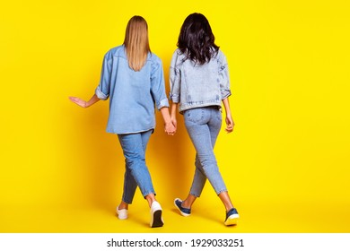 Full body rear portrait of two girls hold each other hand walking weekend isolated on yellow color background