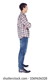 Full body right side view portrait of smiling young man with crossed arms on his chest wearing metal frame glasses, checkered shirt, blue jeans and black shoes isolated on white background