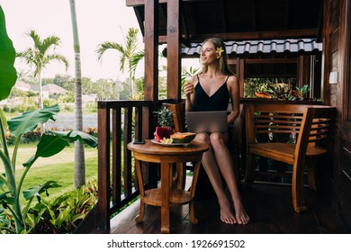 Full body of satisfied female freelancer enjoying summer morning in outdoor cafe and looking away while working on laptop during vegan breakfast